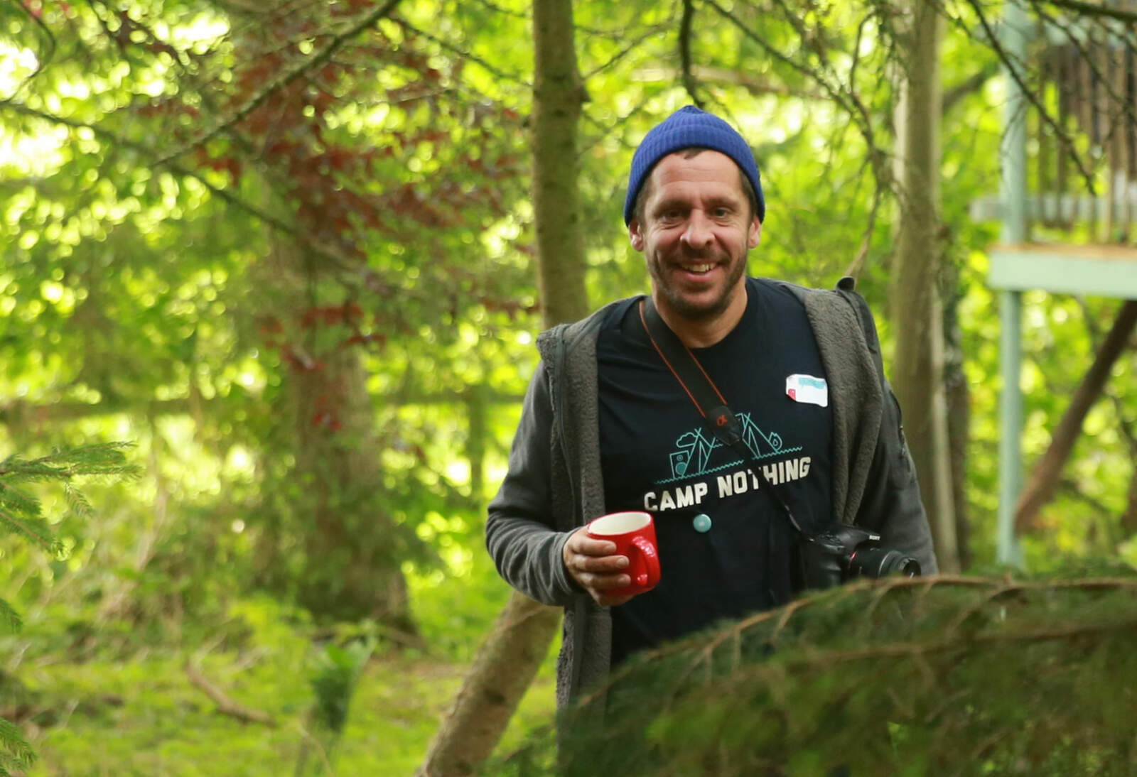 Dan from the Good for Nothing team walks through the woods with a cup of coffee.