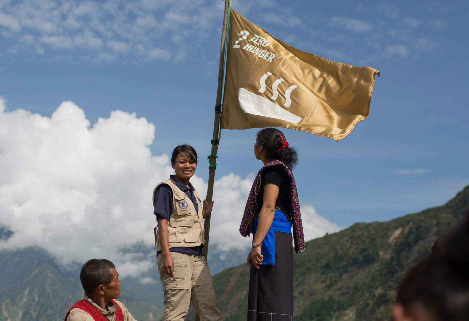 A photo of people holding a flag with one of the Global Goals icons.