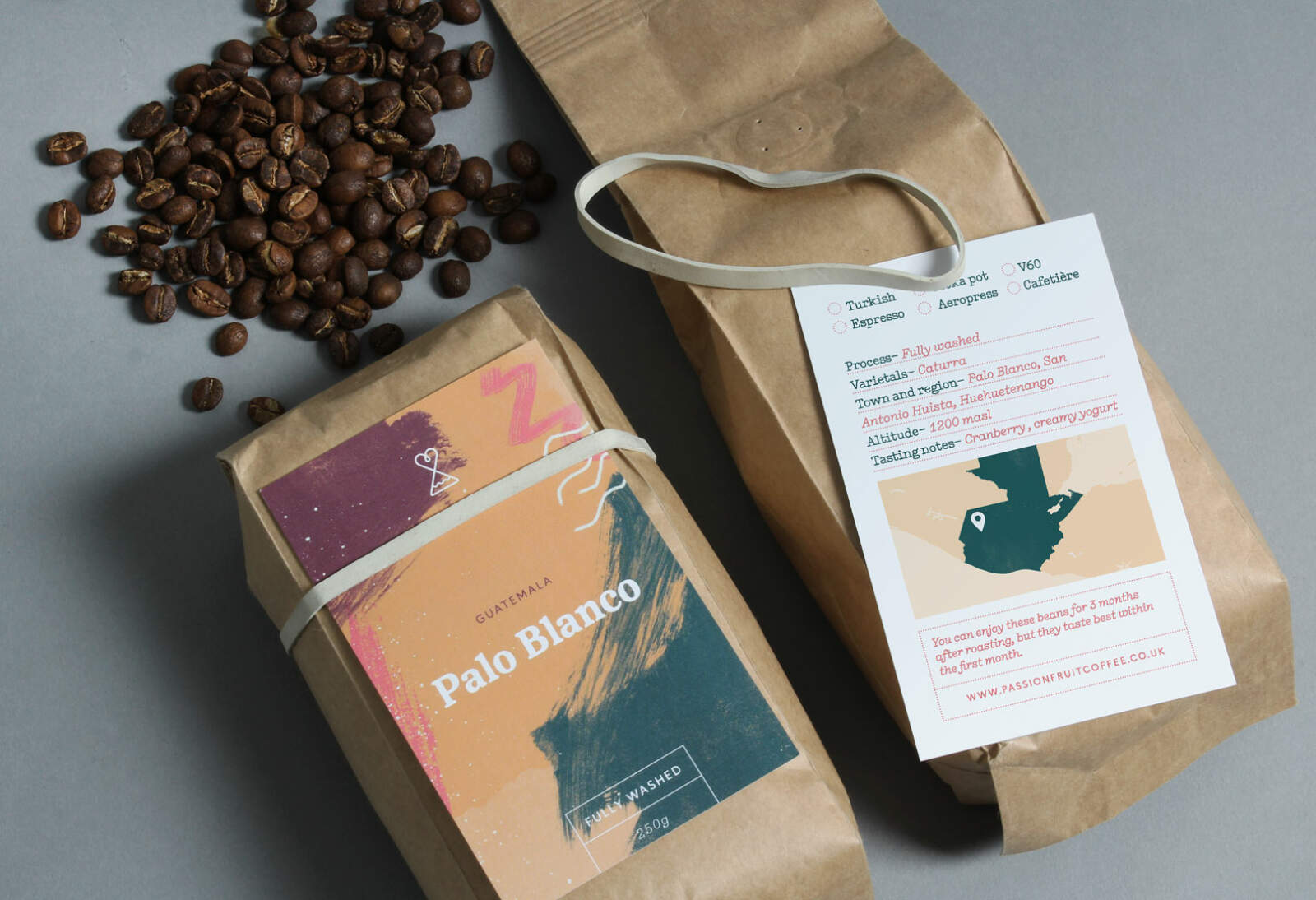 Passion Fruit packaging using the branding system we designed. White elastic bands are used to attach labels to to the coffee packs.