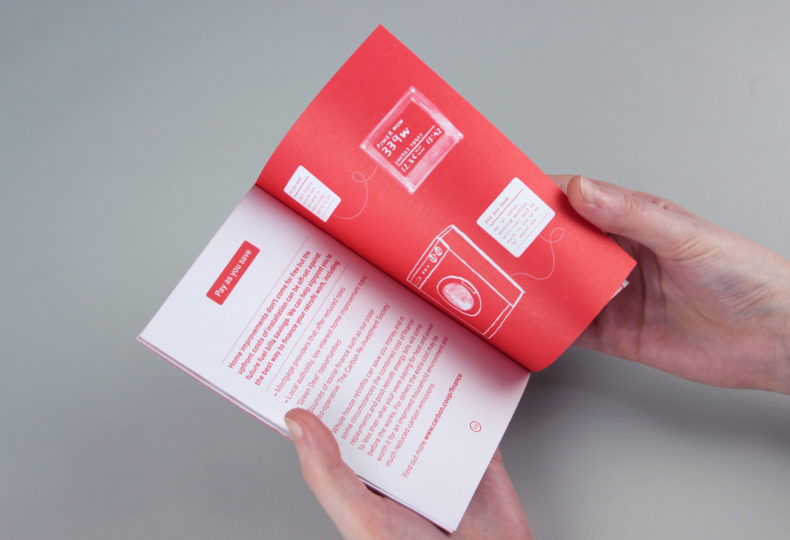 Hands hole open a Carbon Coop booklet, showing type layout and illustrative branding style.
