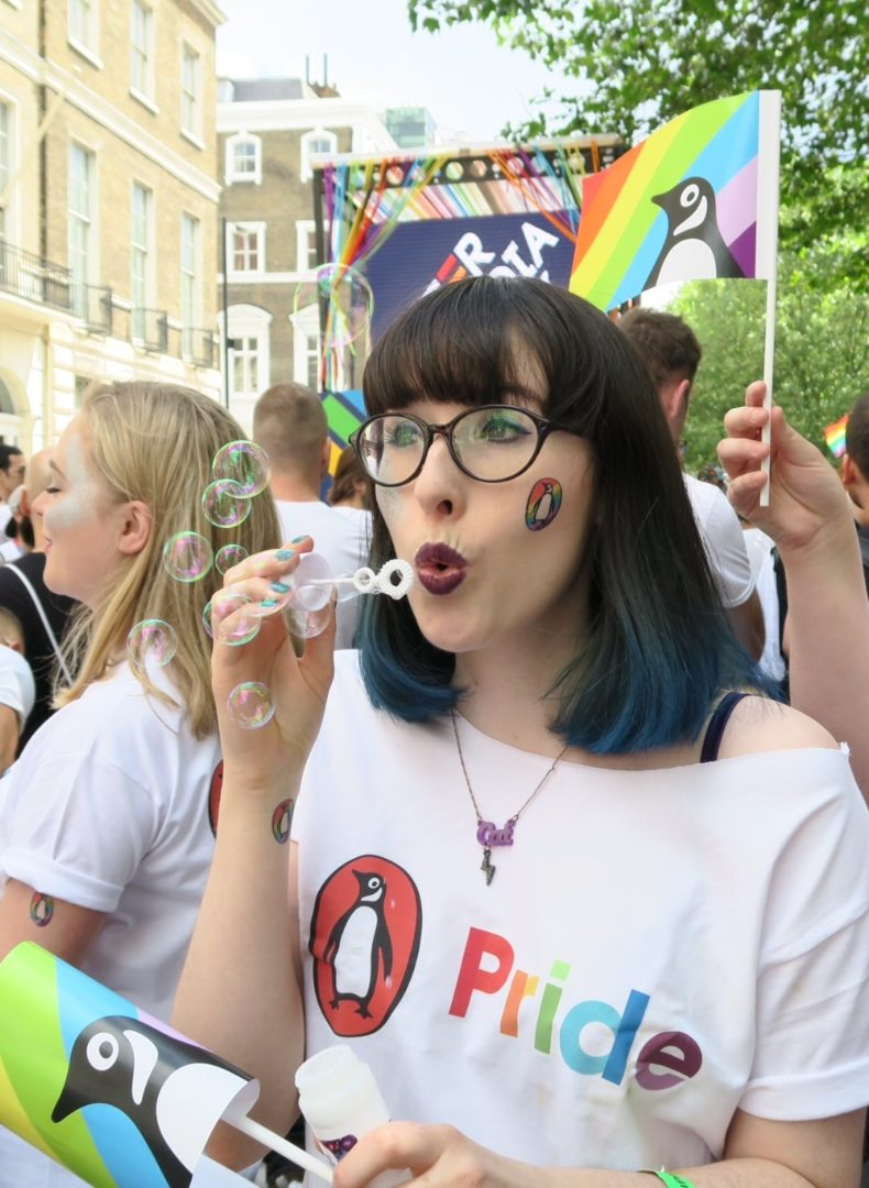 People at the Pride festival wearing Penguin Pride branded t-shirts, waving flags and carrying posters.