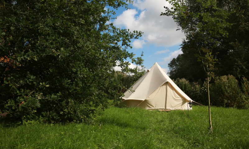A bell tent in the woods at the Camp Nothing event.