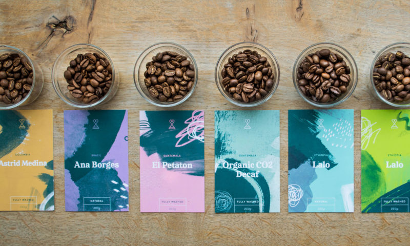 Jars of coffee beans on a table next to branded cards/labels for Passion Fruit Coffee.