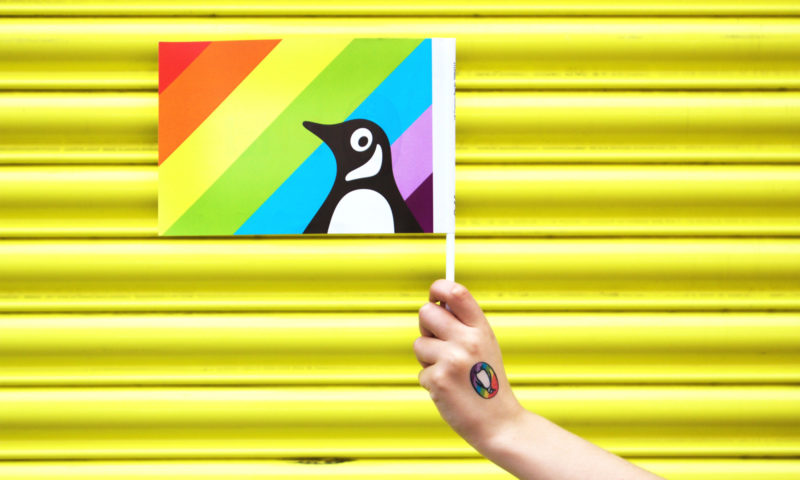 Penguin Pride flag held by a hand wearing a branded temporary tattoo.